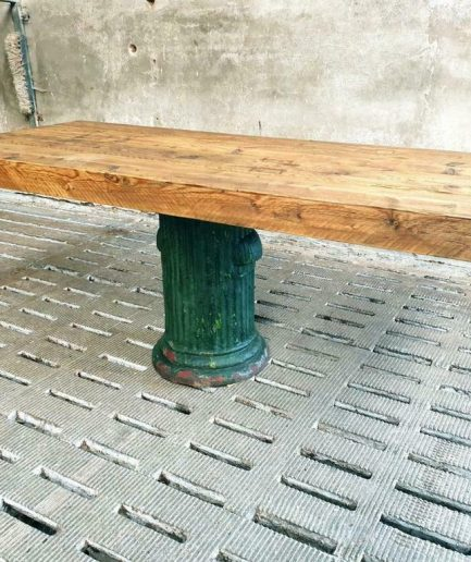 Industrial dining table made of old beams on an antique cast iron leg